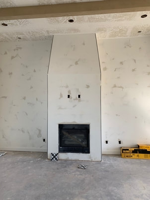drywall around fireplace in large living room