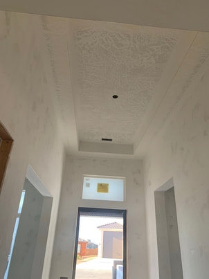 drywall finishing in main entrance of new home with high ceiling